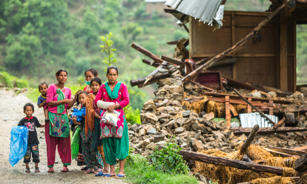 A family beside a damaged house near Naglebhare, Nepal.